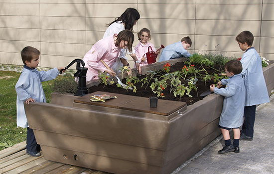 children standing around a planter box