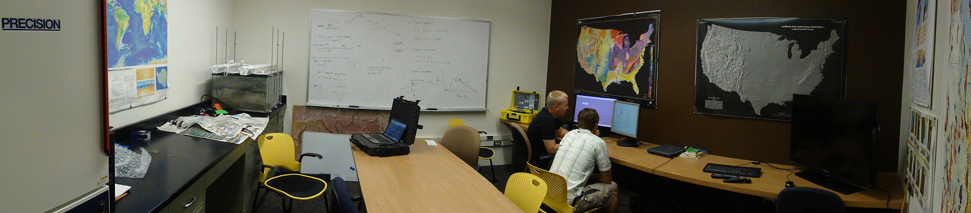 two people sitting at desk looking at computer